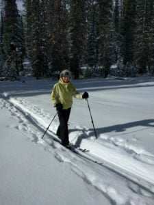 Woman skis through the forest at Deception Creek.
