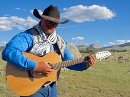 Cowboy sings with a guitar on the range.