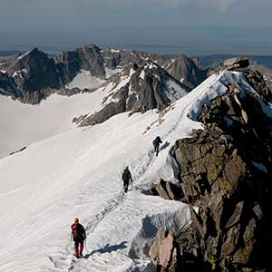Three climbers walk a snowy ridge on Gannett Peak