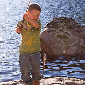 little boy holds up a fish on the shore of the reservoir