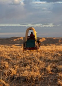 A covered wagon makes its way across the high prairie at sunset