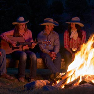 A group of guest ranch guests gather around a campfire for songs and stories.
