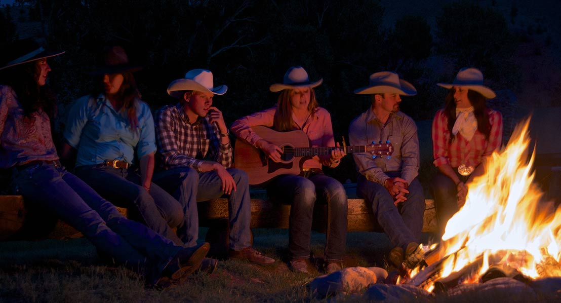 Dude ranch guests sit around a campfire.