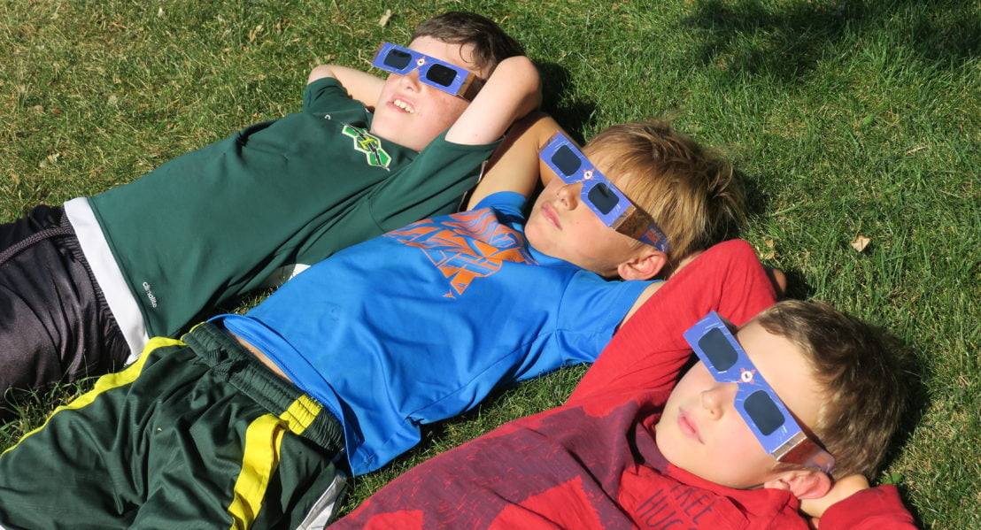 Three boys watching the eclipse on the lawn
