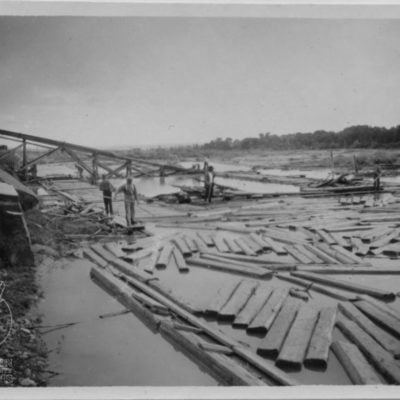 Image of tie hacks floating ties down the Wind River for use in building railroads. Photo courtesy of Fremont County Museums