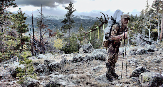 Jared packs his elk out with beautiful scenery behind him.
