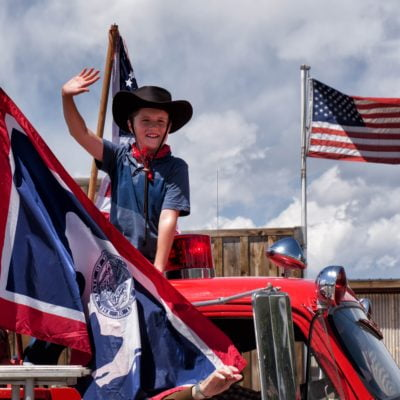 Little boy on an old fire truck with Wyoming and American flag in Dubois, WY