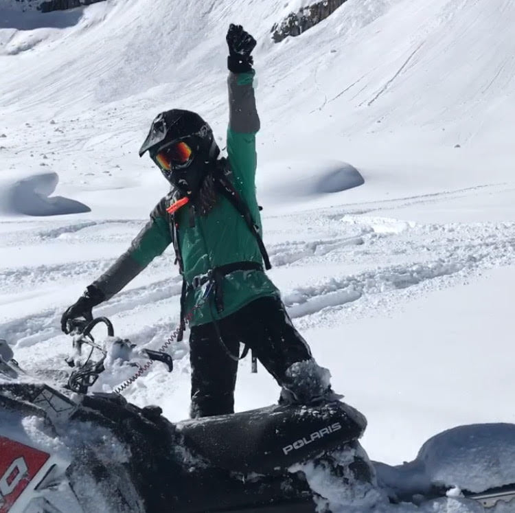 Woman celebrates on snowmobile