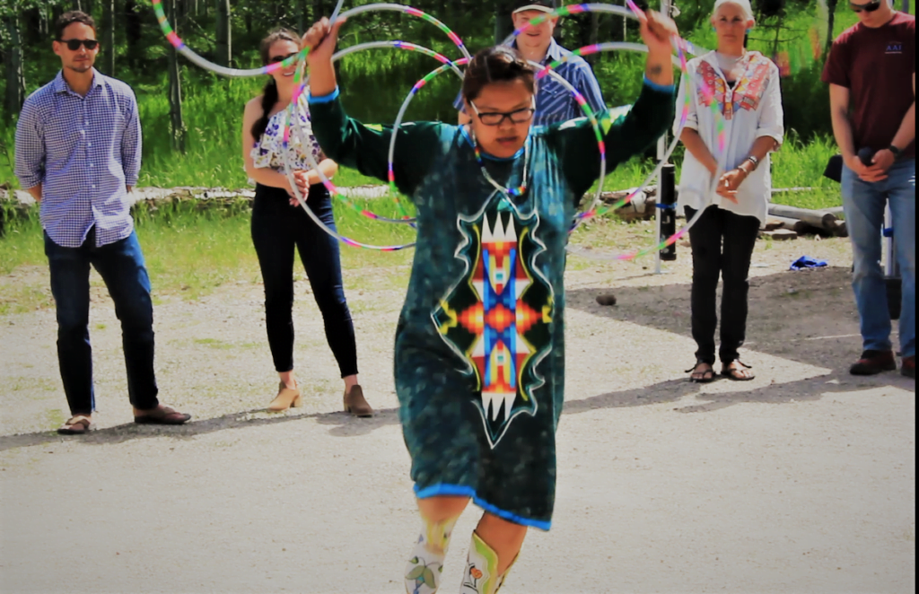 Native American woman performing a hoop dance for observers.