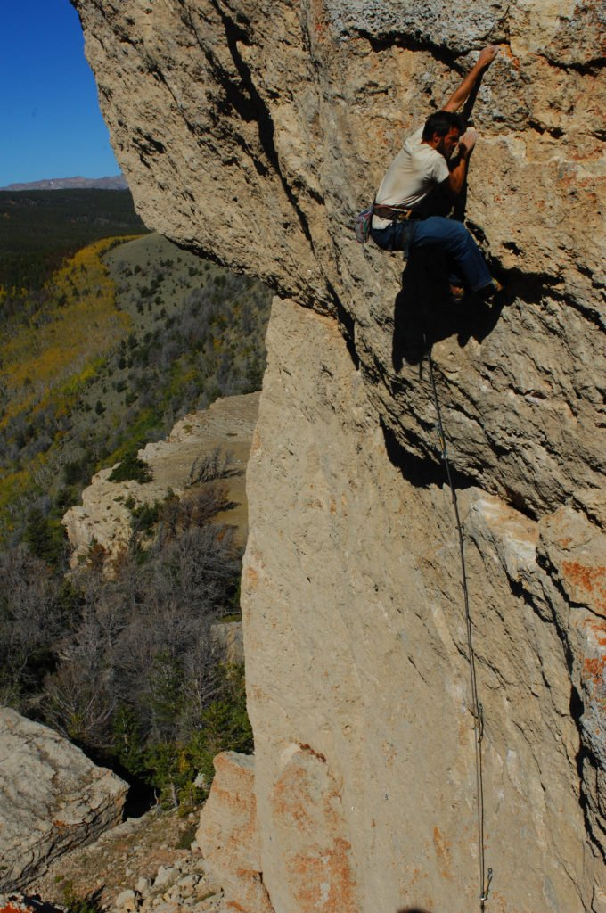Climber on a rock face with fall colors in Wind River Country, Wyoming