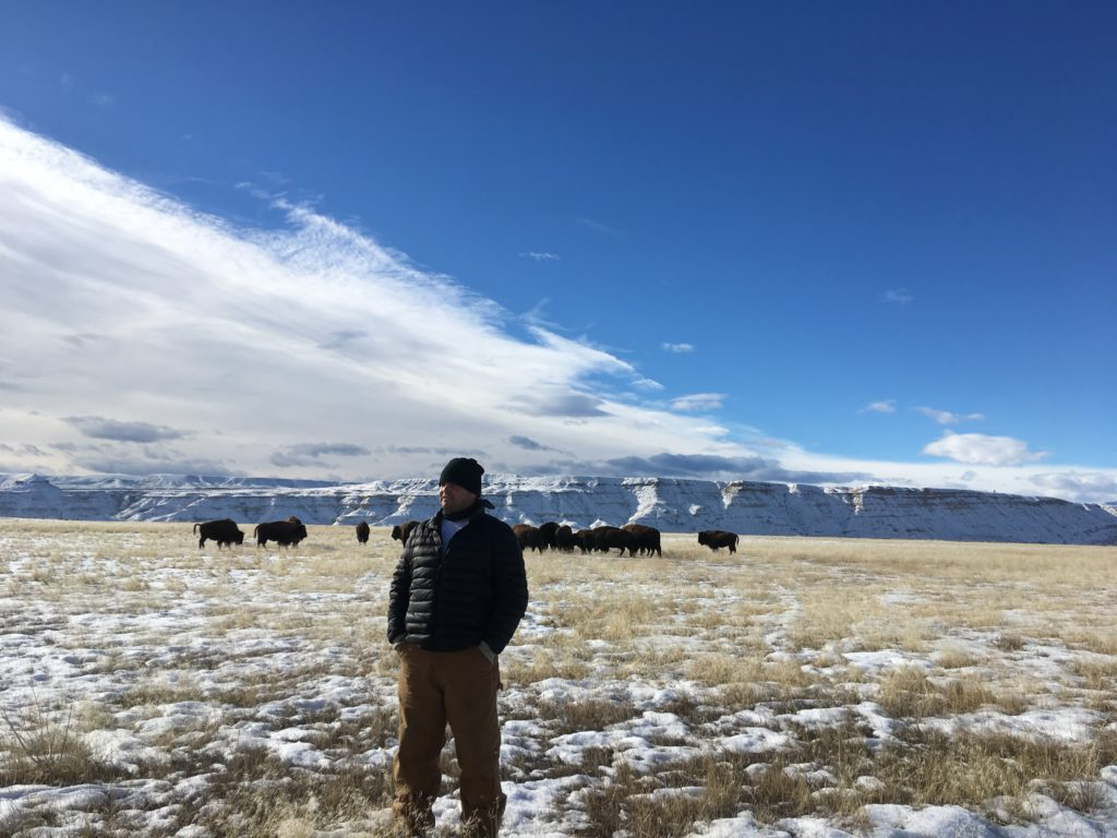 Jason Baldes with a herd of bison on the Native American reservation of Wyoming.